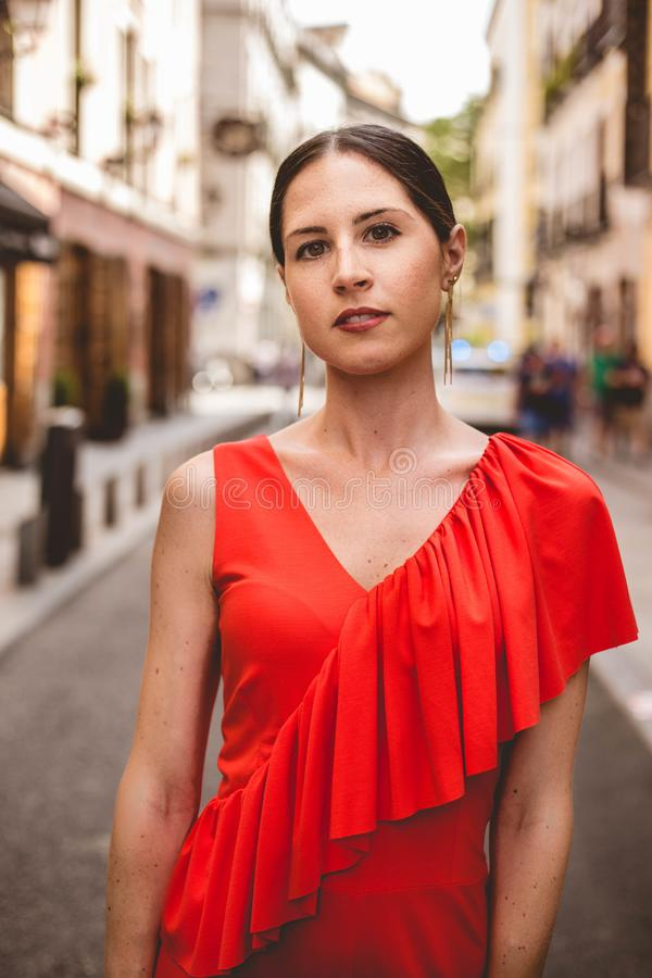 Portrait of beautiful brunette young woman with topknot hairstyle wearing red ruffles dress walking on the street. Fashion photo. Looking to the camera royalty free stock images