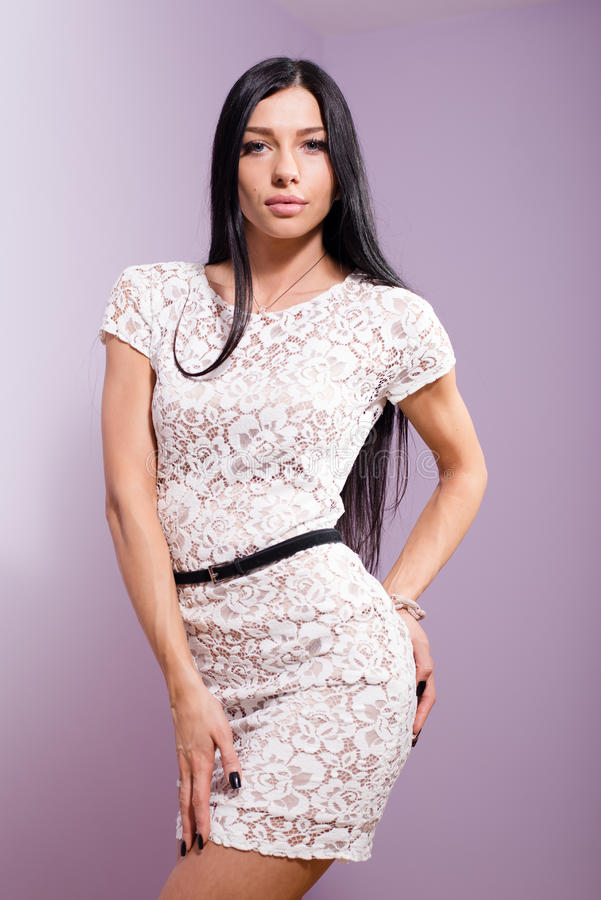 Portrait of beautiful brunette young woman in white lace dress posing stock image