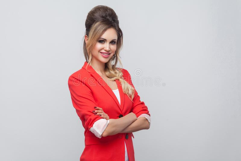Portrait of beautiful business lady with hairstyle and makeup in red fancy blazer, standing, folding arm and looking at camera. With toothy smile. indoor studio royalty free stock image