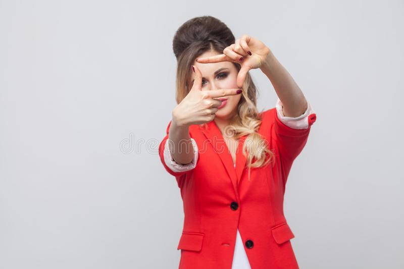 Portrait of beautiful business lady with hairstyle and makeup in red fancy blazer, standing and looking at camera with cropping. Composition gesture. indoor royalty free stock photo