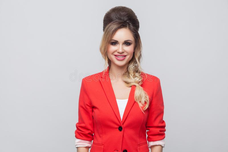 Portrait of beautiful business lady with hairstyle and makeup in red fancy blazer, standing and looking at camera with toothy. Smile. indoor studio shot royalty free stock images