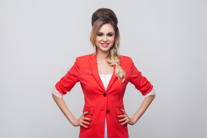 Portrait of beautiful business lady with hairstyle and makeup in red fancy blazer, standing and looking at camera with toothy. Smile and hands on waist. studio royalty free stock photography