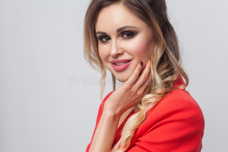 Portrait of beautiful business lady with hairstyle and makeup in red fancy blazer standing and looking at camera, touching her. Face and toothy smiling. indoor royalty free stock photos