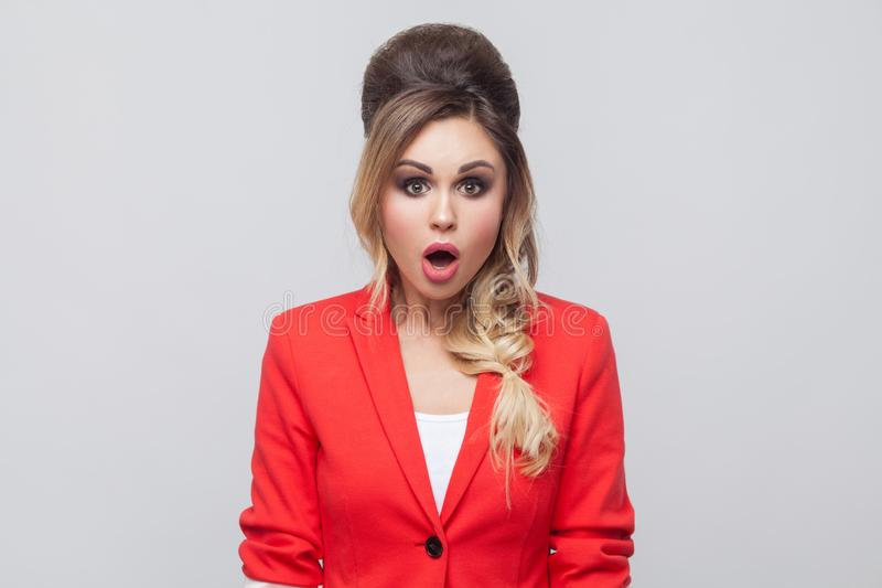 Portrait of beautiful business lady with hairstyle and makeup in red fancy blazer, standing and looking at camera with. Unbelievable face. indoor studio shot stock images