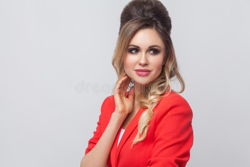 Portrait of beautiful business lady with hairstyle and makeup in red fancy blazer standing, touching her face, looking away and. Smiling. indoor studio shot royalty free stock image