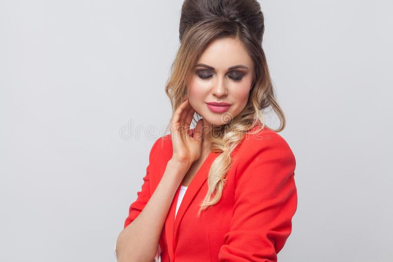 Portrait of beautiful business lady with hairstyle and makeup in red fancy blazer standing and touching her face and smiling with. Closed eyes. indoor studio stock images