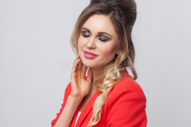 Portrait of beautiful business lady with hairstyle and makeup in red fancy blazer standing and touching her face and smiling with. Closed eyes. indoor studio royalty free stock photos