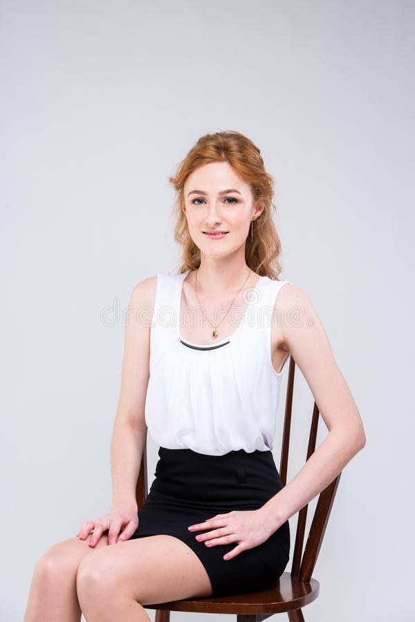 Young beautiful woman with long red, curly hair sitting on a wooden chair on a white background in the studio. Dressed in a white royalty free stock image