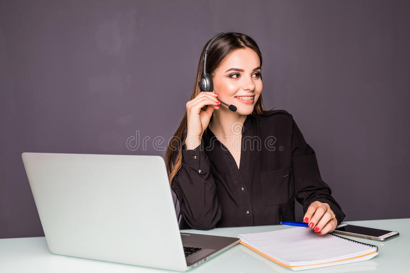 Portrait of beautiful business woman working at her desk with headset and laptop in office royalty free stock photos