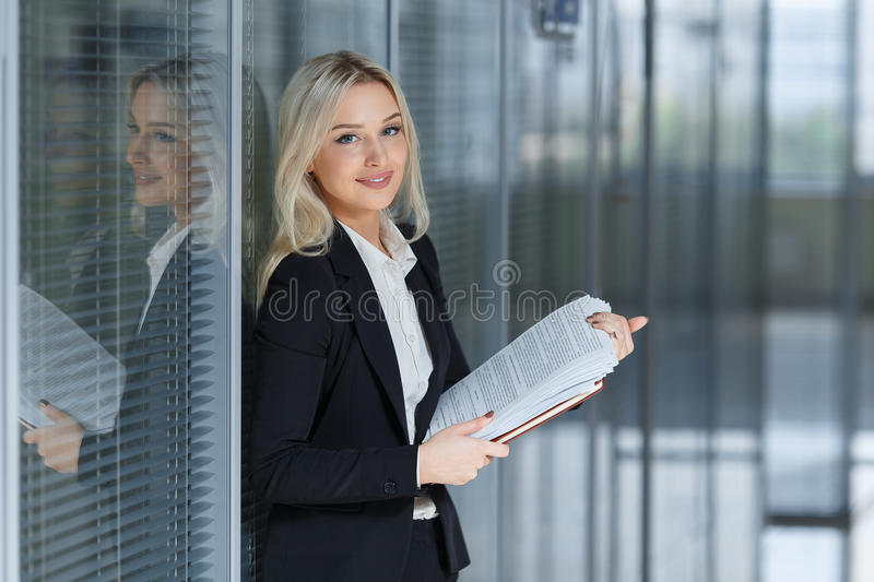 Portrait of beautiful businesswoman smiling and standing with folder in the office stock images