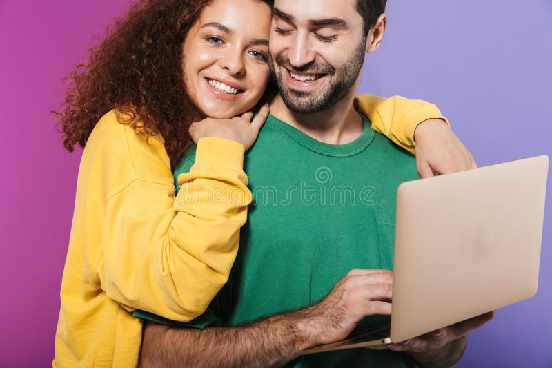 Portrait of beautiful caucasian couple in colorful clothing smiling and using laptop computer together royalty free stock photo