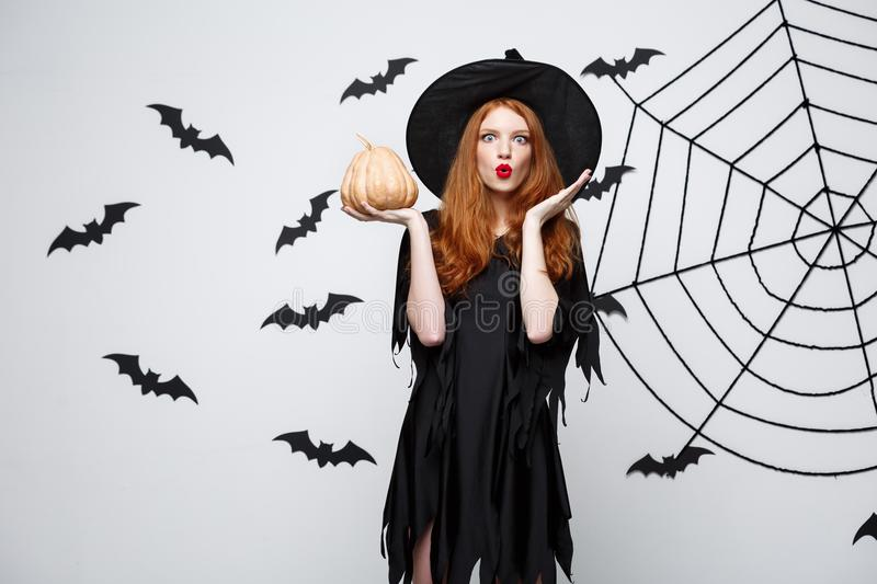 Portrait of beautiful caucasian witch holding pumpkin for celebrating Halloween. stock photography