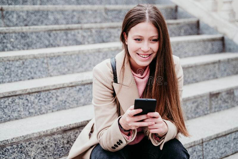 Portrait of beautiful caucasian woman sitting on stairs using mobile phone. Urban, technology and lifestyle concept royalty free stock photography