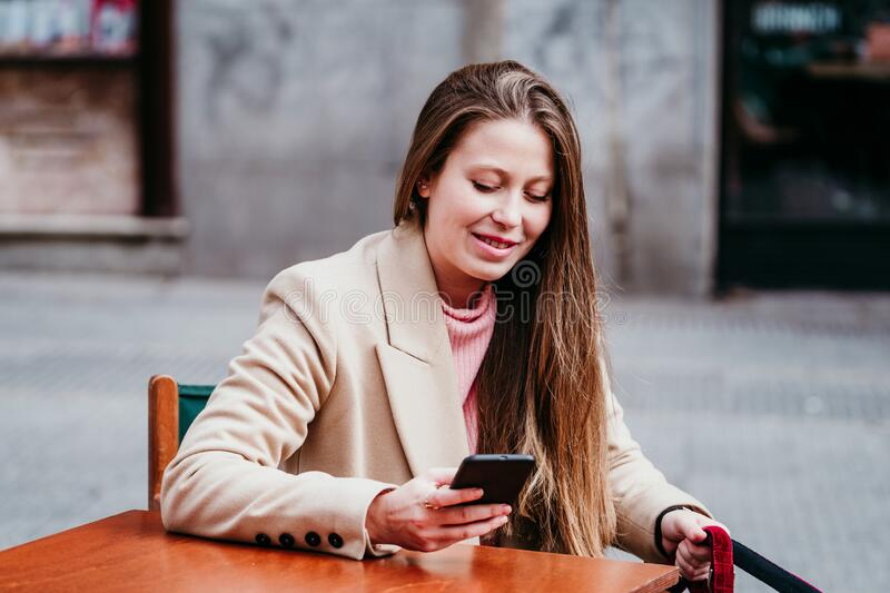Portrait of beautiful caucasian woman on a terrace using mobile phone. Urban, technology and lifestyle concept royalty free stock photo
