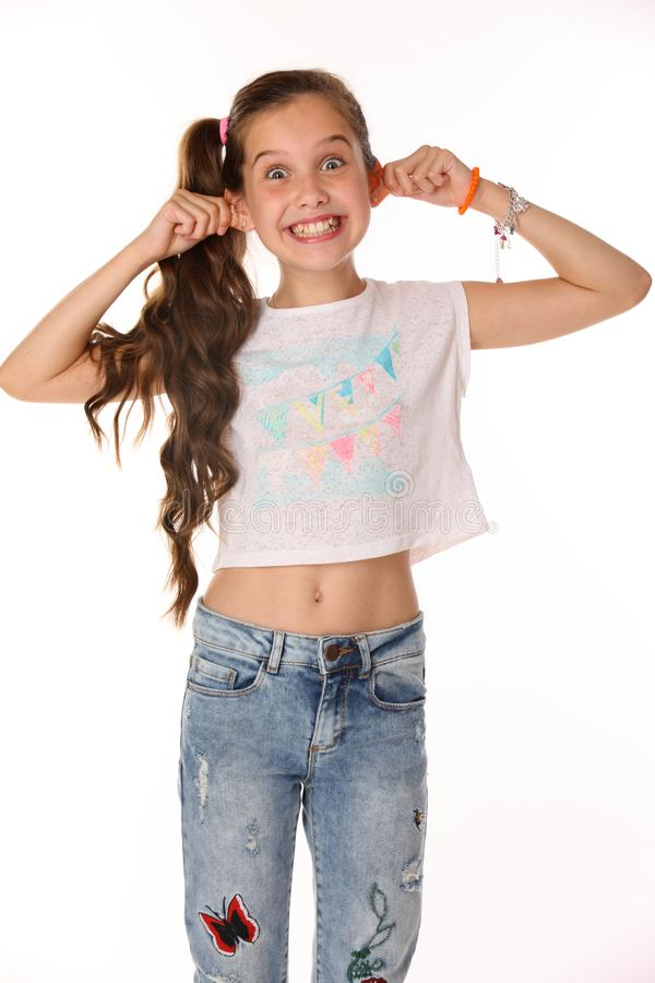 Portrait of beautiful cheerful brunette child girl builds a smiley face ape royalty free stock image
