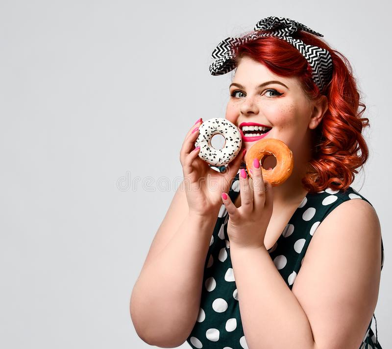Portrait of beautiful cheerful fat plus size woman pin-up wearing a polka-dot dress isolated over light background, eating a donut. Unk food, Slimming, weight royalty free stock photo
