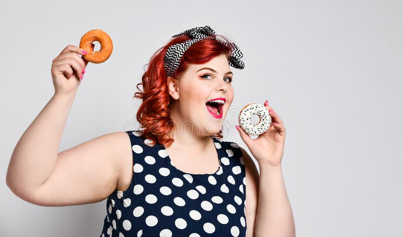 Portrait of beautiful cheerful fat plus size woman pin-up wearing a polka-dot dress isolated over light background, eating a donut.  royalty free stock photo