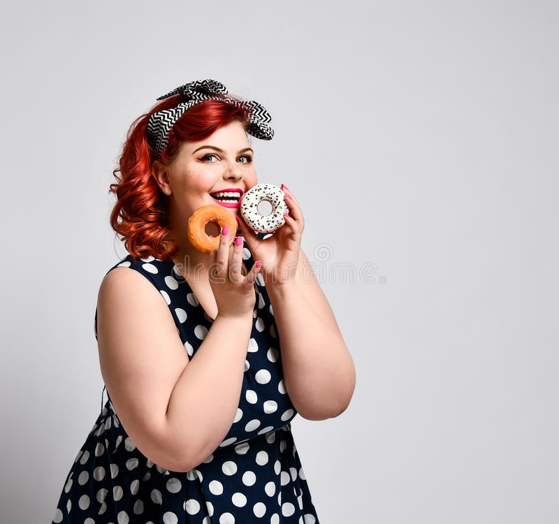 Portrait of beautiful cheerful fat plus size woman pin-up wearing a polka-dot dress isolated over light background, eating a donut. Unk food, Slimming, weight royalty free stock image