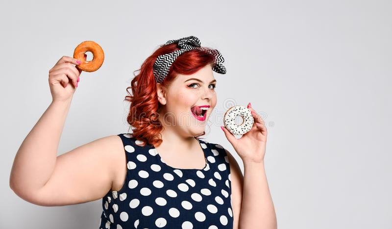 Portrait of beautiful cheerful fat plus size woman pin-up wearing a polka-dot dress isolated over light background, eating a donut.  stock image