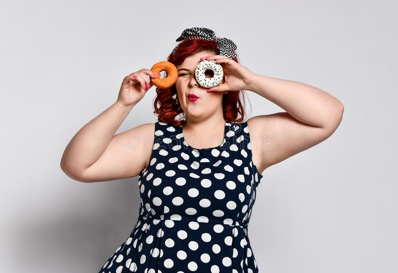 Portrait of beautiful cheerful fat plus size woman pin-up wearing a polka-dot dress isolated over light background, eating a donut. Unk food, Slimming, weight stock images