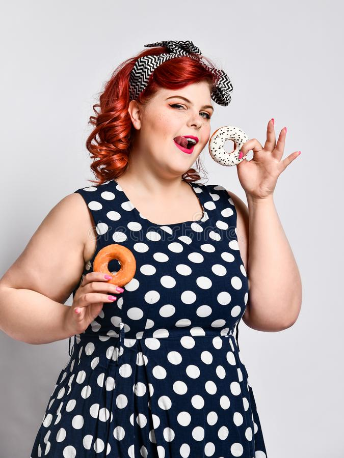 Portrait of beautiful cheerful fat plus size woman pin-up wearing a polka-dot dress isolated over light background, eating a donut. Diet, dieting concept stock photography