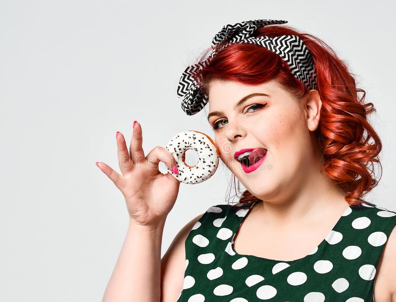 Portrait of beautiful cheerful fat plus size woman pin-up wearing a polka-dot dress isolated over light background, eating a donut. Diet, dieting concept stock photo