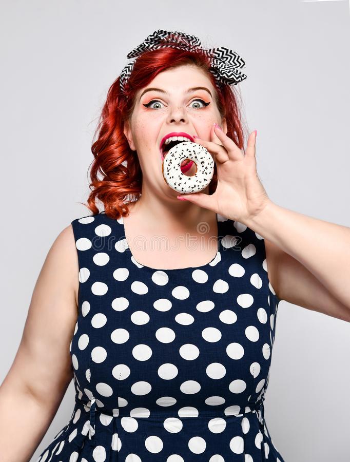 Portrait of beautiful cheerful fat plus size woman pin-up wearing a polka-dot dress isolated over light background, eating a donut stock images