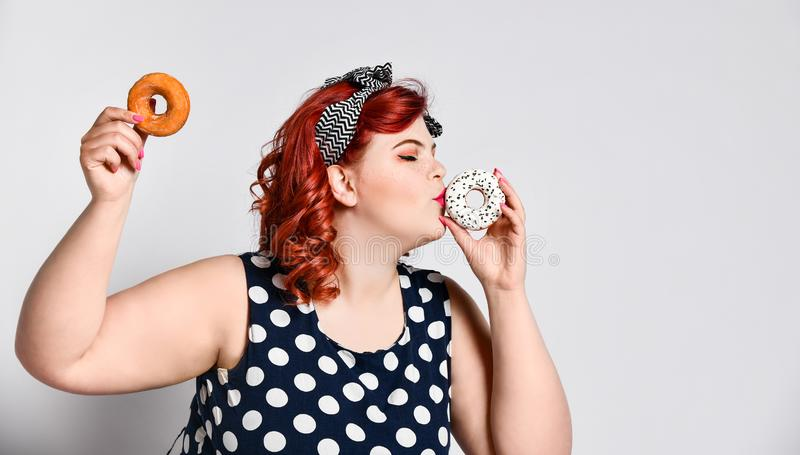 Portrait of beautiful cheerful fat plus size woman pin-up wearing a polka-dot dress isolated over light background, eating a donut stock photo