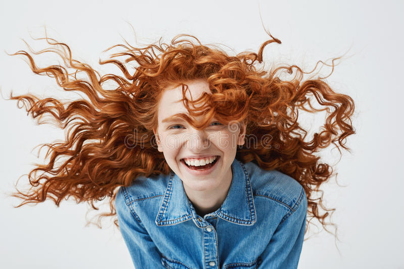 Portrait of beautiful cheerful redhead girl with flying curly hair smiling laughing looking at camera over white royalty free stock image