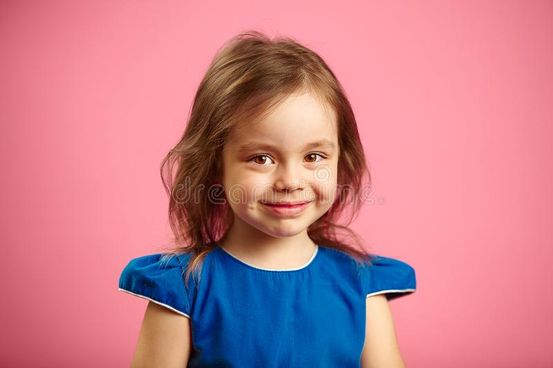 Portrait of beautiful child girl with charming look on blue background. royalty free stock images