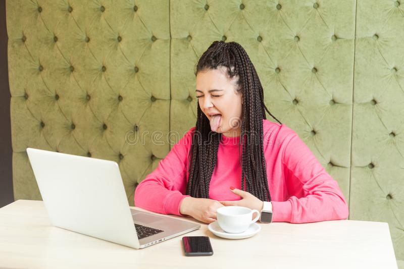Portrait of beautiful childish funny young girl freelancer with black dreadlocks hairstyle in pink blouse sitting and showing. Tongue out on webcamera laptop stock photo