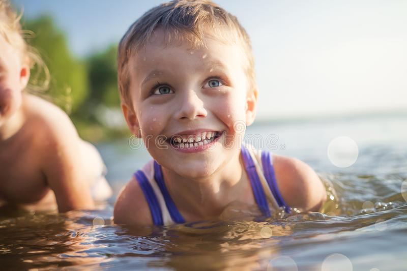 Portrait of beautiful children laugh and bathe in the sea. boy smiles and swims in lake. Good mood kids on summer lake. royalty free stock image