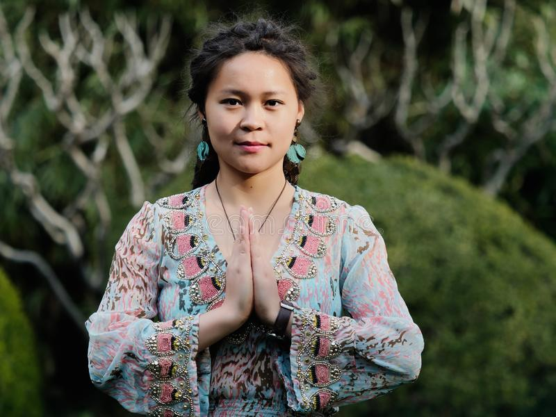 Portrait of a beautiful Chinese girl with cute dreadlocks palms together as prayer`s position in sunny day royalty free stock photography