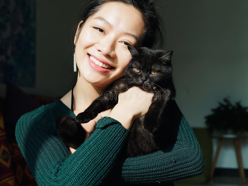 Portrait of beautiful Chinese young girl hug her cute British Shorthair Cat who has amazing orange eyes at home and smile stock images