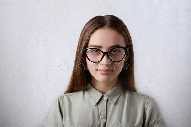 A portrait of beautiful confident girl with long straight hair wearing big glassses looking at camera isolated over grey backgroun royalty free stock photography