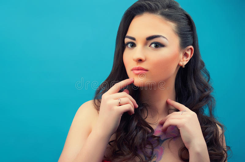 Portrait of the beautiful contemplative girl on the blue background. Stylish hairstyle and makeup. Young female model stock image