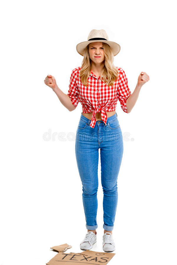Portrait of beautiful country girl hitchhiking over white background. Portrait of angry young beautiful country girl in hat, jeans and shirt hitchhiking stock photo