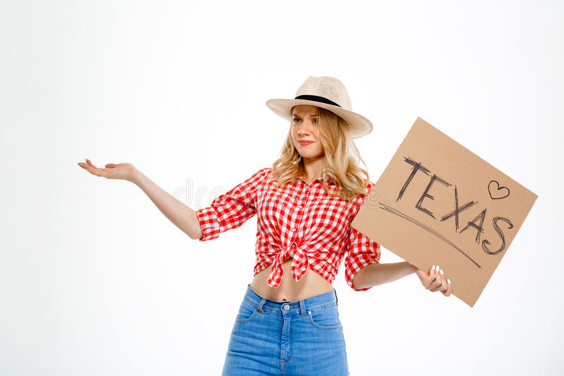 Portrait of beautiful country girl hitchhiking over white background. Portrait of young beautiful country girl in hat, jeans and shirt hitchhiking over white royalty free stock photos