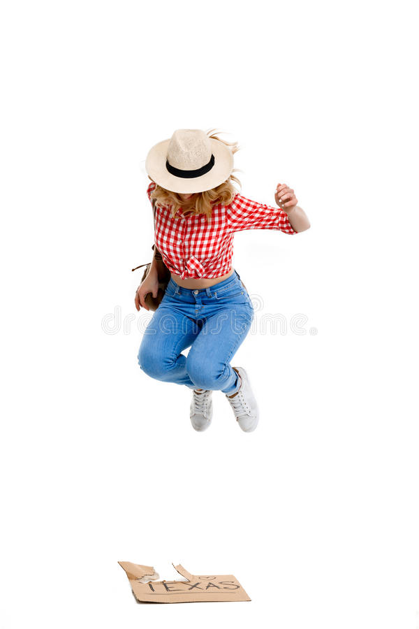 Portrait of beautiful country girl hitchhiking over white background. Portrait of young beautiful country girl in hat, jeans and shirt hitchhiking, jumping over royalty free stock image