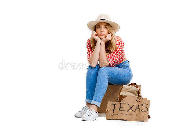 Portrait of beautiful country girl hitchhiking over white background. Portrait of young beautiful country girl in hat, jeans and shirt hitchhiking, looking at royalty free stock photography