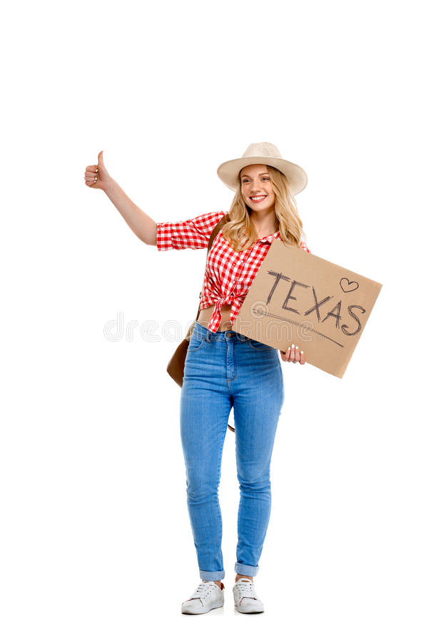 Portrait of beautiful country girl hitchhiking over white background. Portrait of young beautiful country girl in hat, jeans and shirt hitchhiking, smiling over stock images