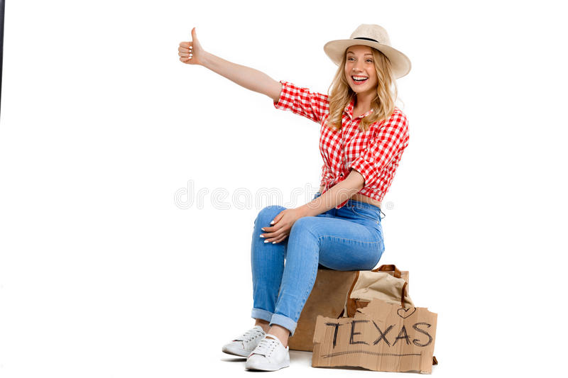 Portrait of beautiful country girl hitchhiking over white background. royalty free stock photo