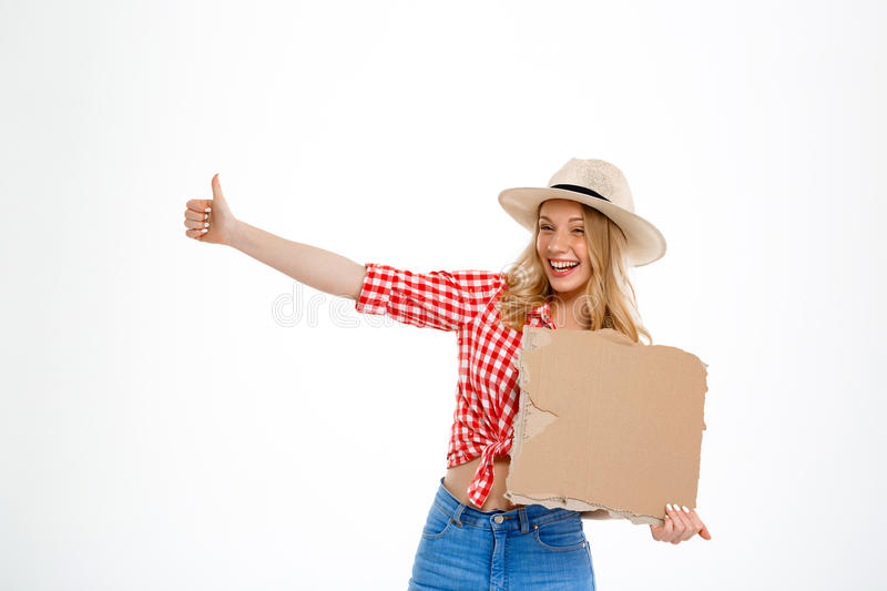 Portrait of beautiful country girl hitchhiking over white background. Portrait of young beautiful country girl in hat, jeans and shirt hitchhiking, smiling over royalty free stock photo