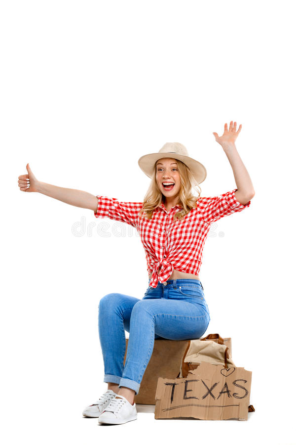 Portrait of beautiful country girl hitchhiking over white background. Portrait of young beautiful country girl in hat, jeans and shirt hitchhiking, smiling over royalty free stock photography