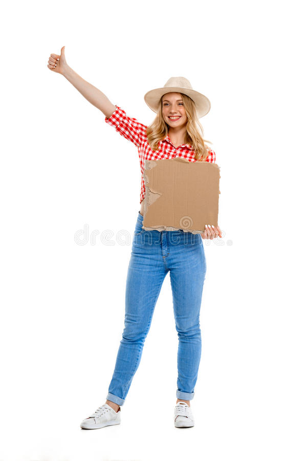 Portrait of beautiful country girl hitchhiking over white background. Portrait of young beautiful country girl in hat, jeans and shirt hitchhiking, smiling over royalty free stock image