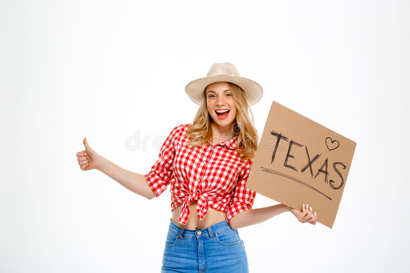 Portrait of beautiful country girl hitchhiking over white background. Portrait of young beautiful country girl in hat, jeans and shirt hitchhiking, smiling stock image