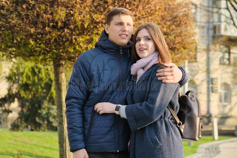 Portrait of beautiful couple in city, happy young man and woman embracing, golden hour royalty free stock image
