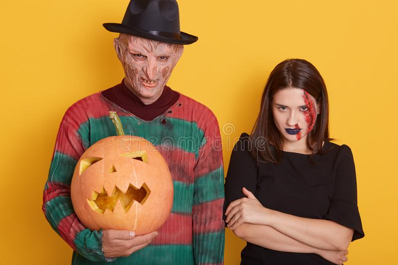 Portrait of beautiful couple with pumpkin isolated over yellow studio background, guy with wrinkled ugly face, wears sweater and royalty free stock image