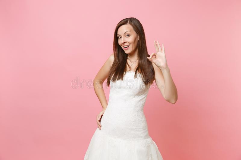Portrait of beautiful curious bride woman in elegant white wedding dress standing and showing OK sign isolated on pink stock photography