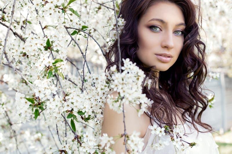 Portrait beautiful cute sweet girl bride with gentle eye make-up full lips in white light dress walks in lush gard stock image
